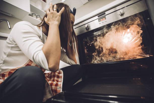 woman failed at dinner - burned oven imagens e fotografias de stock