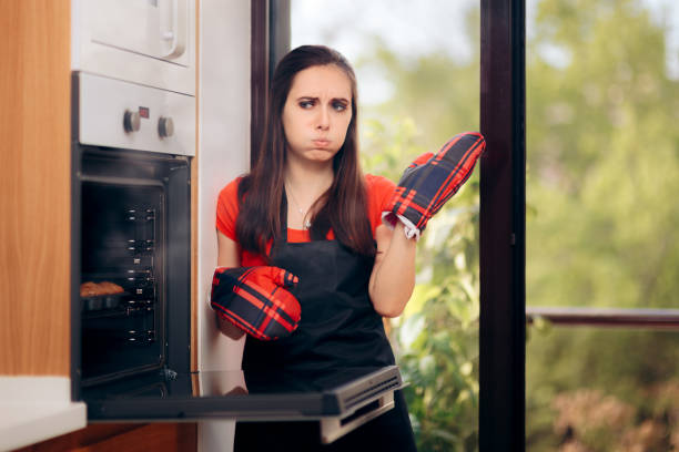 woman failing at baking some muffins in the oven - burned oven imagens e fotografias de stock