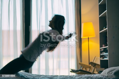 Young female backwards jumping on bed.