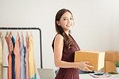 女性ファッションデザイナーが段ボール箱を立って保持しています。