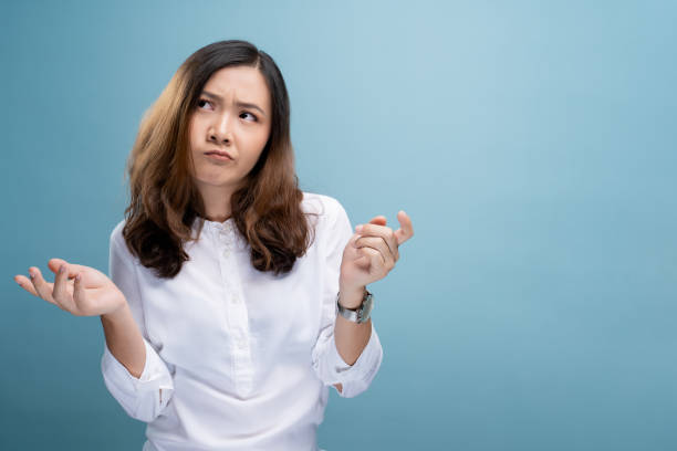 Woman feel confused isolated over blue background stock photo