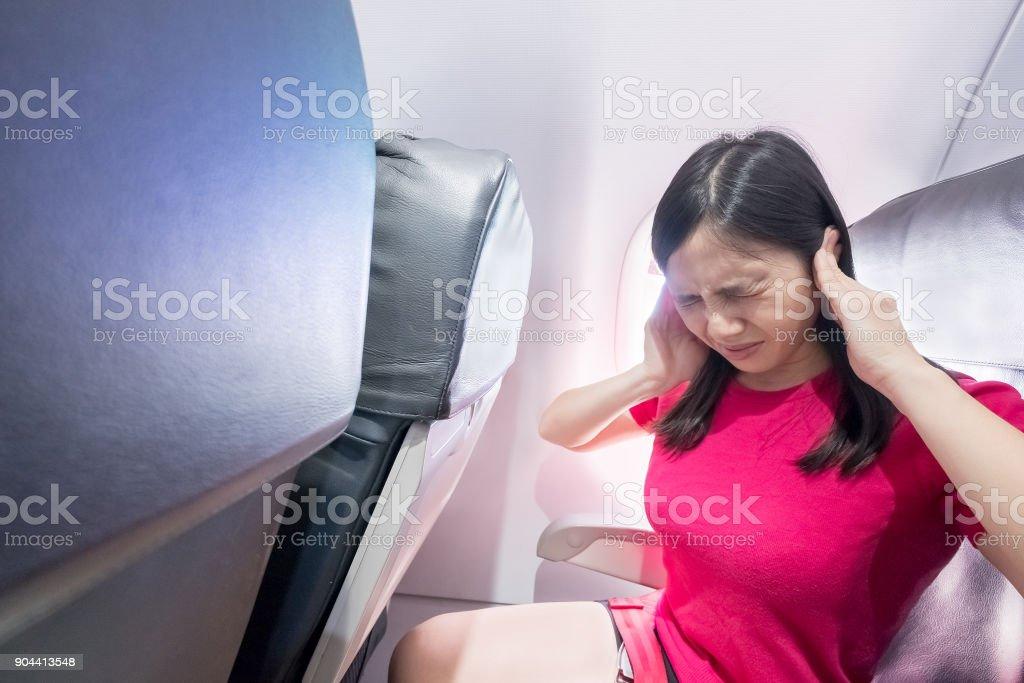 woman feel tinnitus in airplanes stock photo