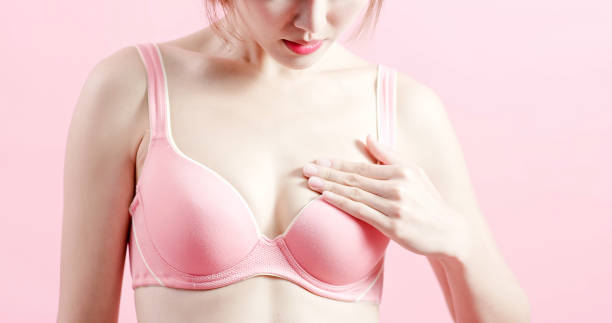 woman feel uncomfortable woman feel uncomfortable and check her chest with prevention breast cancer concept bra stock pictures, royalty-free photos & images