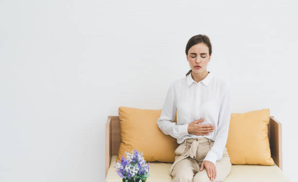 Woman feeling abdominal pain while sitting on sofa at living room Woman feeling abdominal pain while sitting on sofa at living room endometriosis stock pictures, royalty-free photos & images