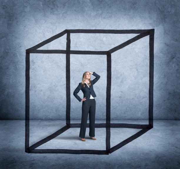 woman feeling boxed in by cube drawn around her - intrappolato foto e immagini stock