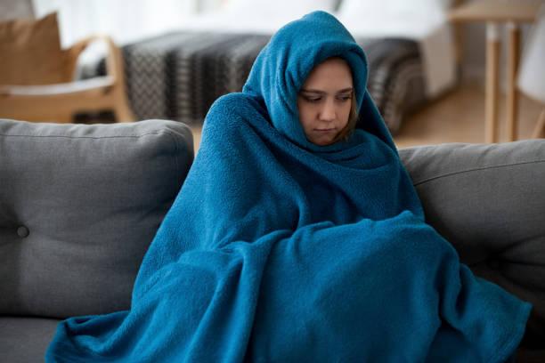 kadın duygu soğuk evde sıcak battaniye ile örtülü - soğukluk stok fotoğraflar ve resimler