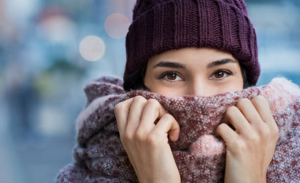 Woman feeling cold in winter Winter portrait of young beautiful woman covering face with woolen scarf. Closeup of happy girl feeling cold outdoor in the city. Young woman holding scarf and looking at camera.