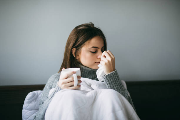 Woman feeling ill, lying in bed while holding a mug and blowing nose stock photo