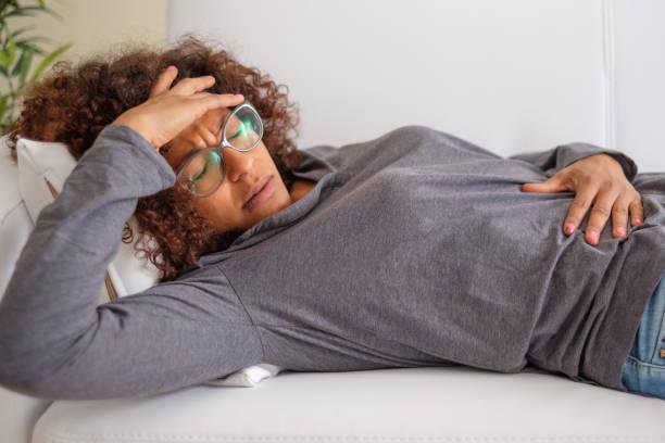 Frau Schmerzen auf dem Bauch liegend auf sofa – Foto