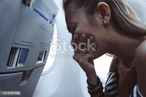 The fear in the plane. The frightened woman has a fear of flying airplane. A passenger traveling on the affected aircraft. Asian tourists with the stress on the flying air plane.