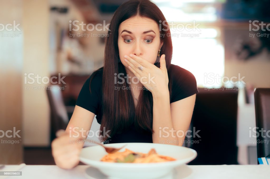 Woman Feeling Sick While Eating Bad Food in a Restaurant stock photo