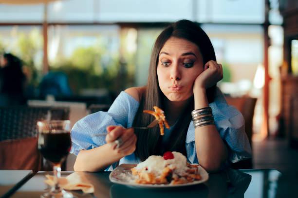 kvinna känsla sjuk medan du äter stor mål tid - matsmältningsbesvär bildbanksfoton och bilder