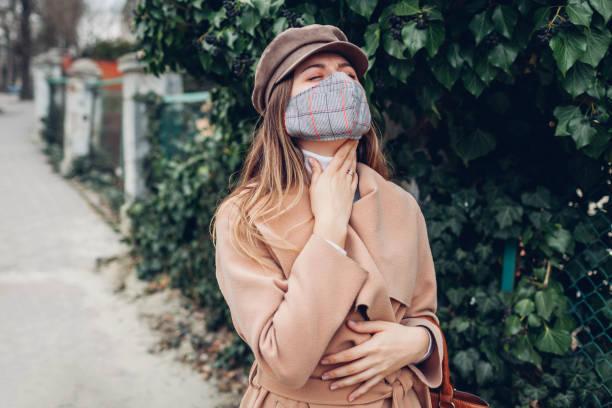Woman feels sore throat wears reusable mask outdoors during coronavirus covid-19 pandemic. Girl feeling sick.