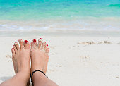 Woman feet and red nails on the beach