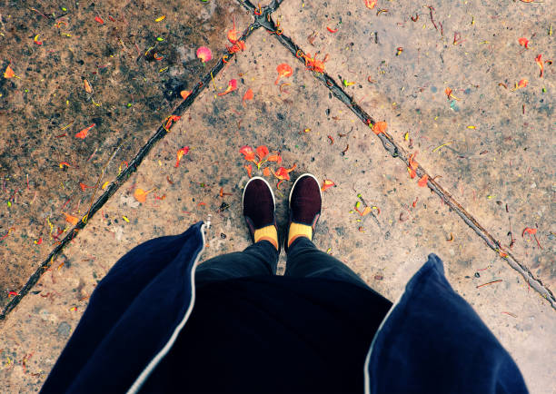 woman feet in black clothes stand with orange petals fall in raining day stock photo