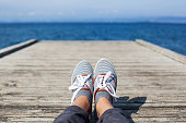 Woman feet in casual shoes on the wooden pier with sea or ocean background