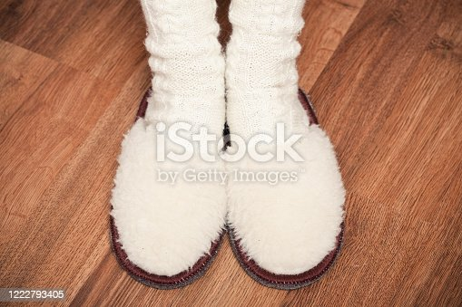 woman feet in knitted woolen socks and fluffy slippers