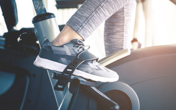 Woman feet is cycling on fitness exercising bike machine Woman feet is cycling on fitness exercising bike machine exercise bike stock pictures, royalty-free photos & images