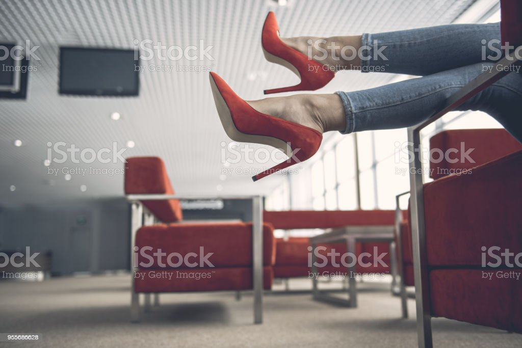 Woman feet locating in modern lounge zone stock photo