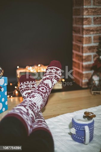 Woman feet near the cup of hot drink in front of fireplace.