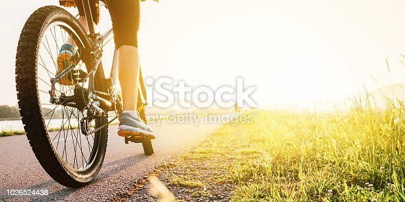 Woman feet on bycikle pedal in sunset light