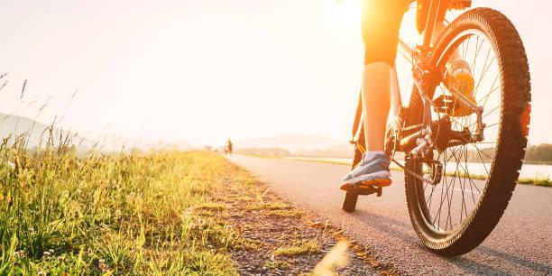 piedi donna su pedale bycikle alla luce del tramonto - ciclismo foto e immagini stock