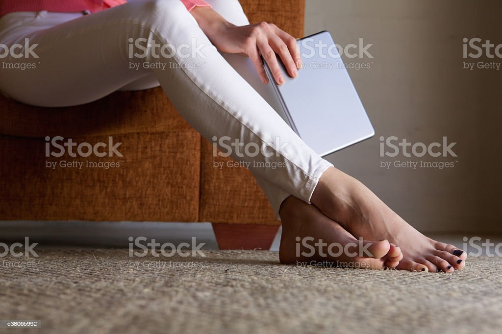 Woman feet on floor at home with digital tablet stock photo