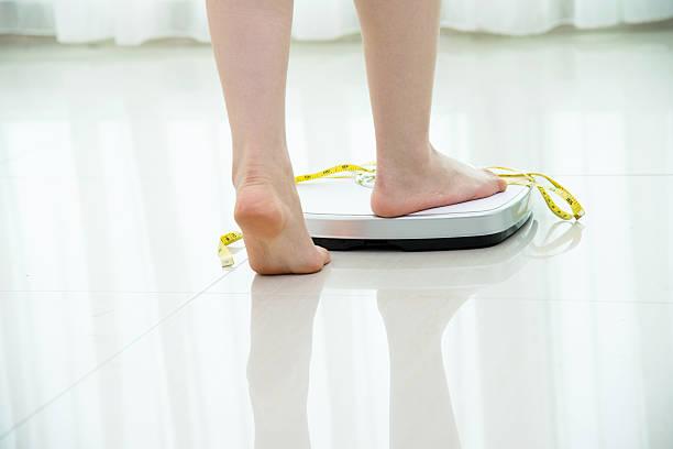 Woman feet on scale stok fotoğrafı