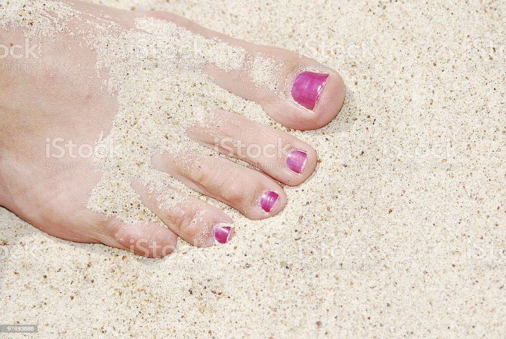 Woman feet on the sunny sand royalty-free stock photo