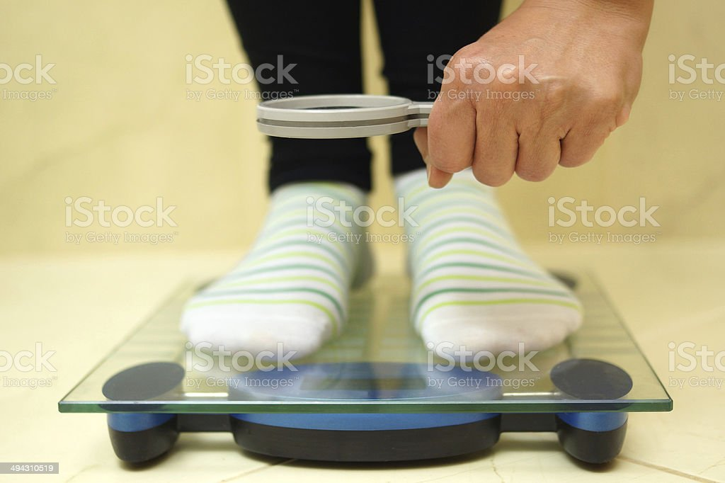 Mujer cuadrados en báscula mirando de aumento de peso - foto de stock