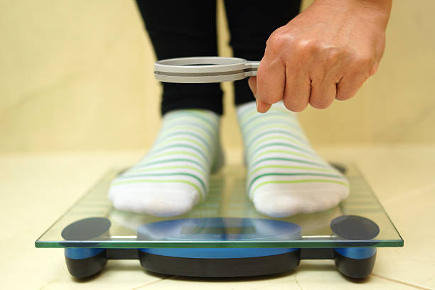 woman feet on weighing scales looking weight over magnifying stock photo