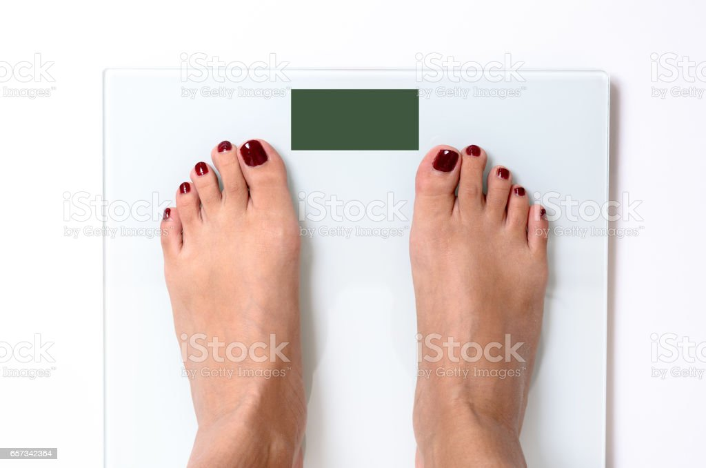 Woman feet on weight scales stock photo