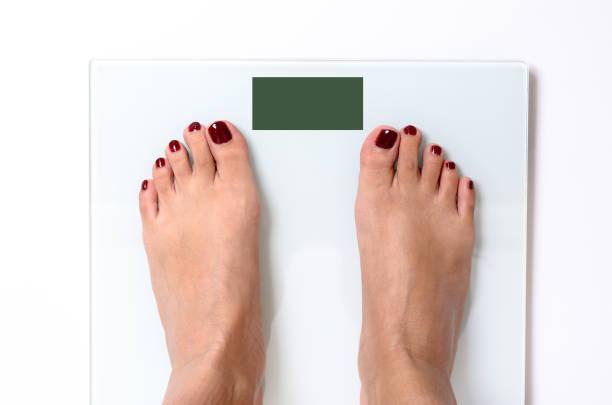 Kadın ayakları üzerinde ağırlık ölçekleri stok fotoğrafı