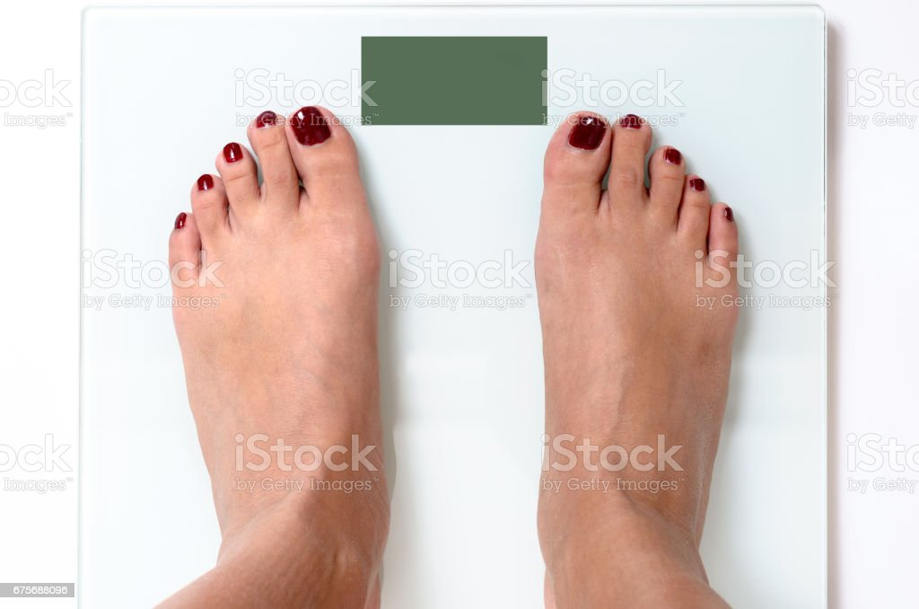 Woman feet on weight scales royalty-free stock photo