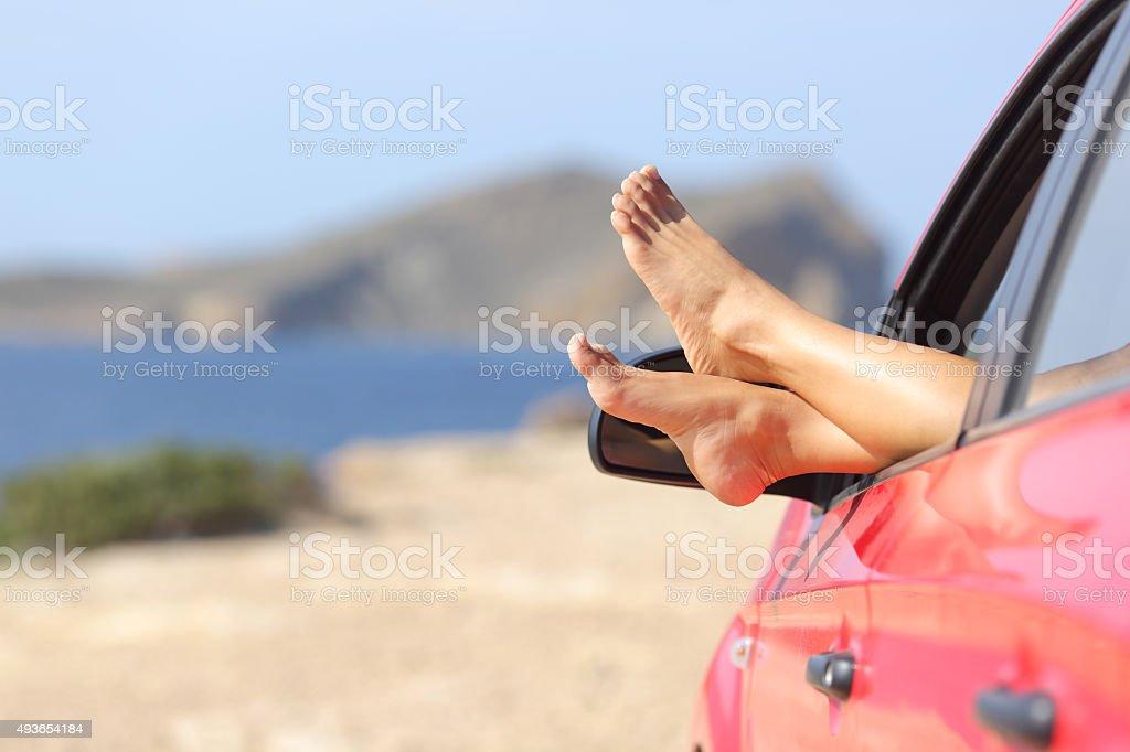 Mulher pés relaxando em um automóvel na praia - foto de acervo