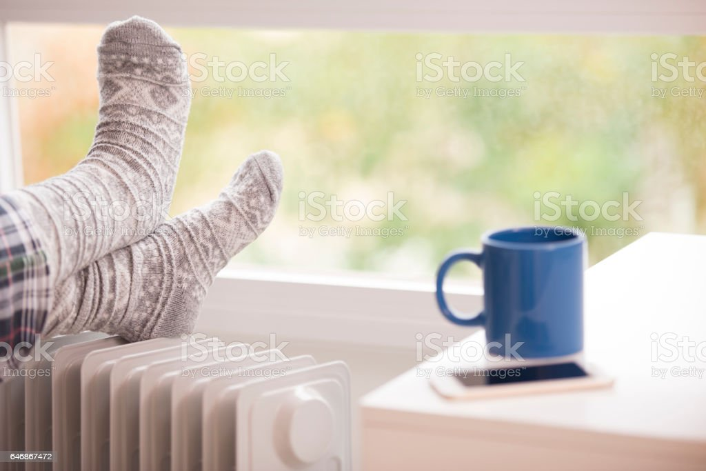 Woman feet resting on the warm radiator. stock photo