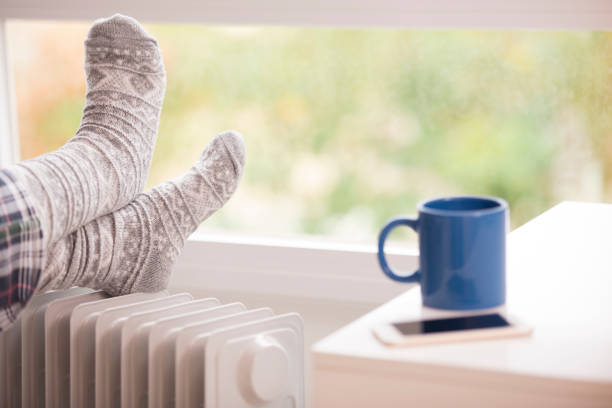 woman feet resting on the warm radiator. - warm house stock photos and pictures