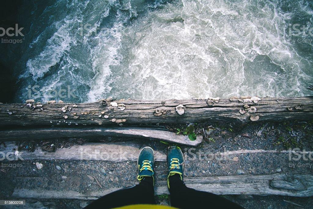 Woman Feet standing on wooden bridge edge over river stock photo