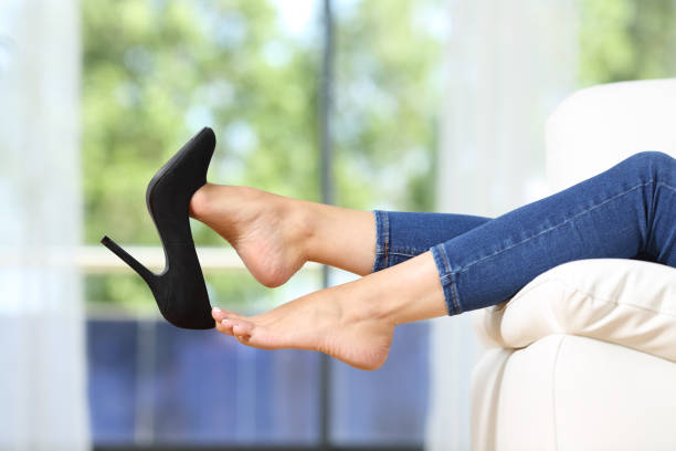 Woman feet taking off shoes resting on a couch Side view close up of beautiful woman feet taking off shoes resting lying on a couch in the living room at home undressing stock pictures, royalty-free photos & images