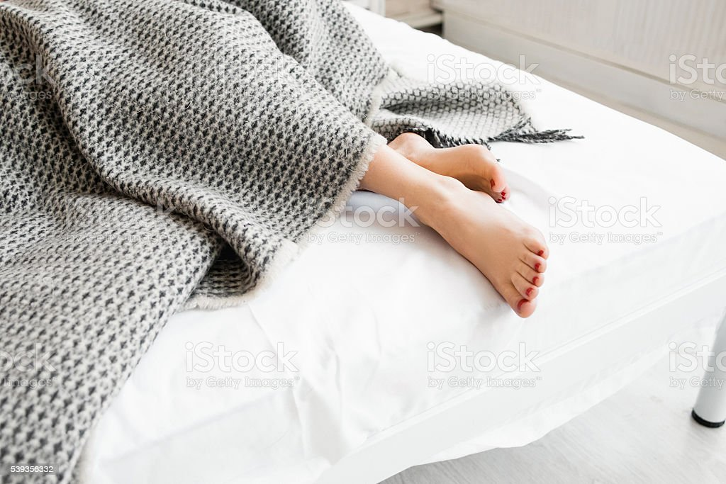 Woman feet under gray blanket sideview stock photo