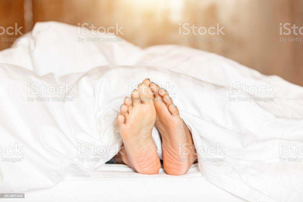 queen bett seitenansicht kissen seitenansicht frau füße unter weißen decke seitenansicht schöne junge mit blauen pediküre auf dem unter weißen seitenansicht junge