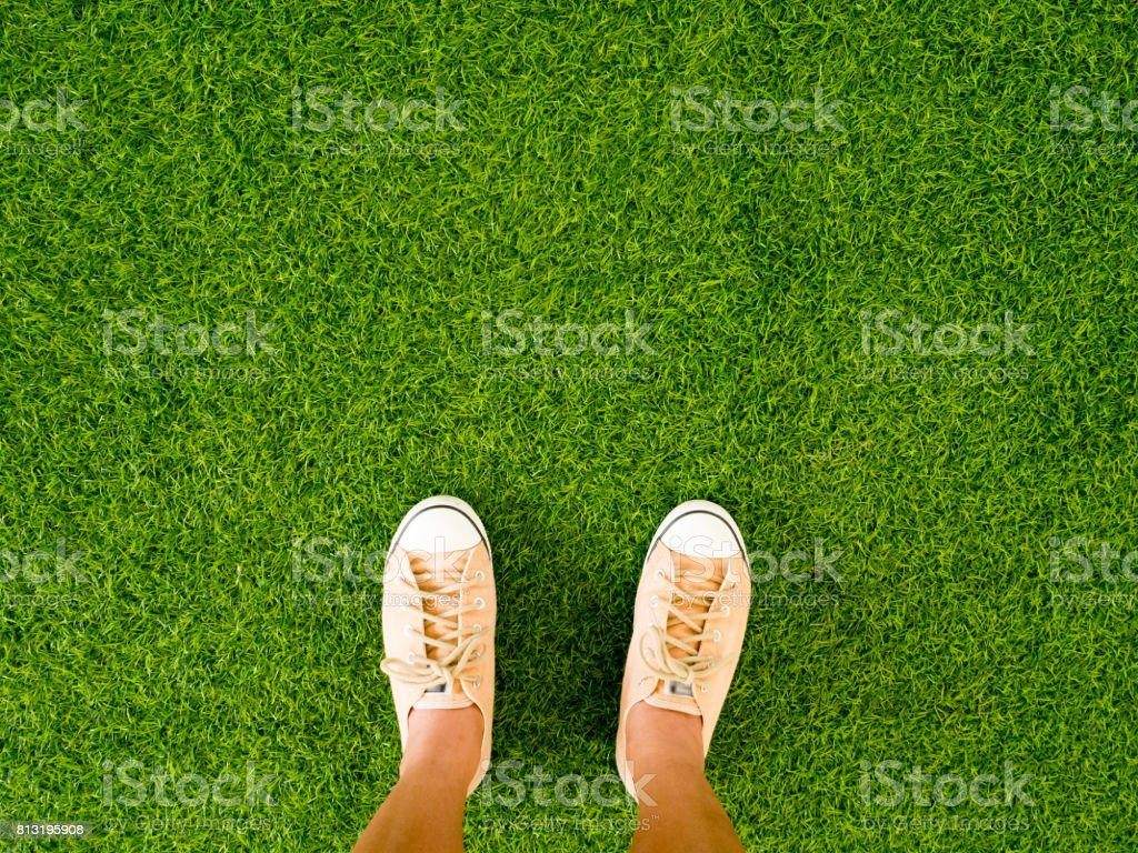 Woman feet wear vintage soft brown sneaker shoes stand on green grass floor. stock photo