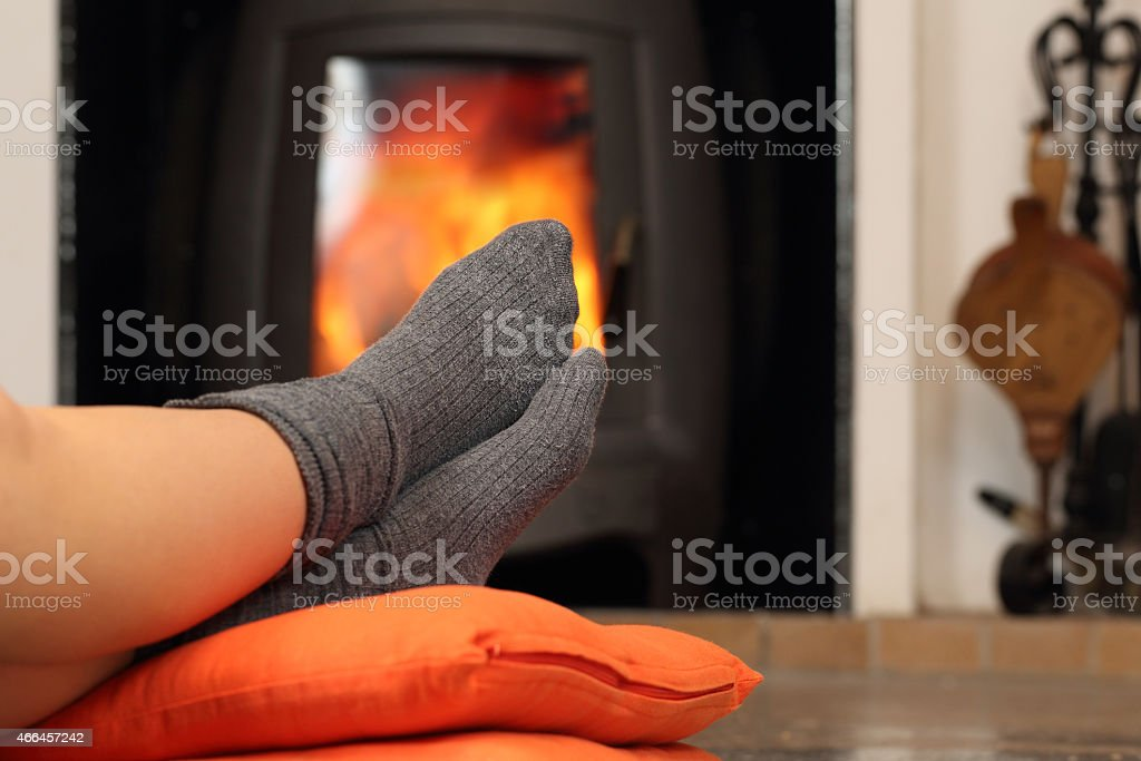 Woman feet with socks resting near fire place stock photo