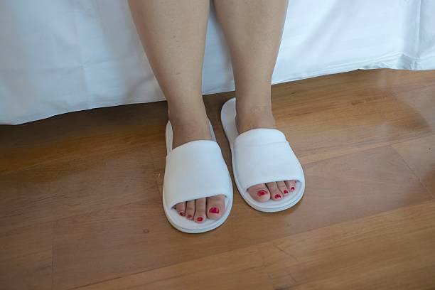 frau füße mit weißen slipper - badmöbel gäste wc stock-fotos und bilder
