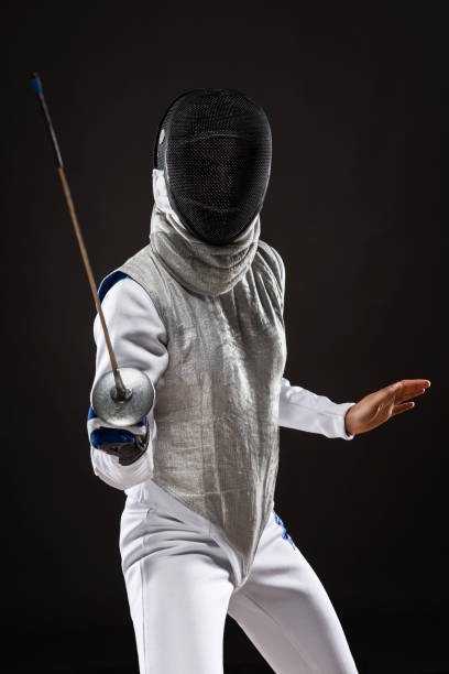 Woman fencer in attacking pose stock photo