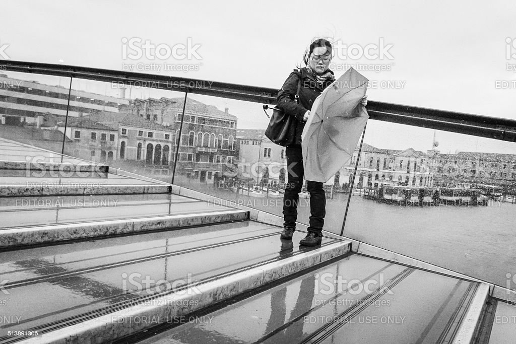 Woman fights with her umbrella on Calatrava Bridge stock photo