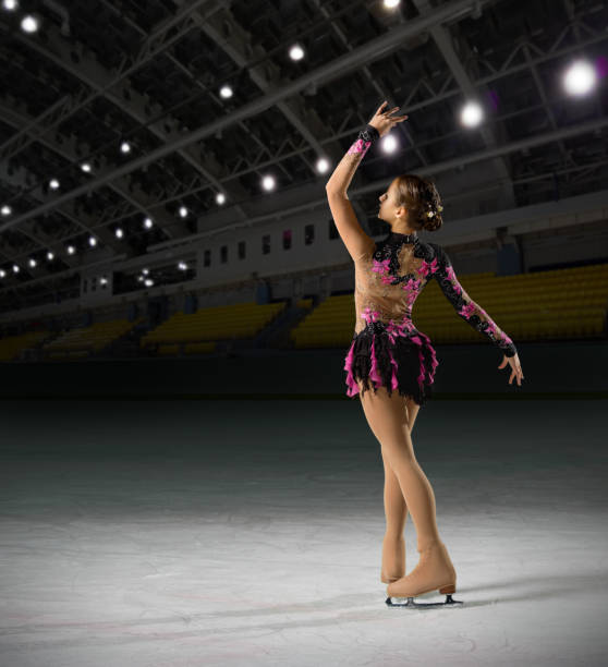 Woman figure skater at sports hall stock photo