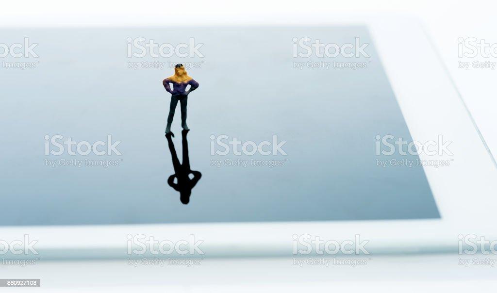 Woman figurine standing on digital tablet stock photo