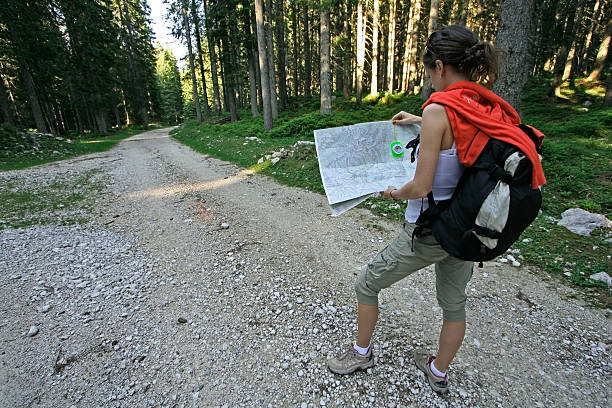 A woman figuring out where to go on her map in the woods young woman holding a map and compass, trying to figure out which way to go fork in the road stock pictures, royalty-free photos & images