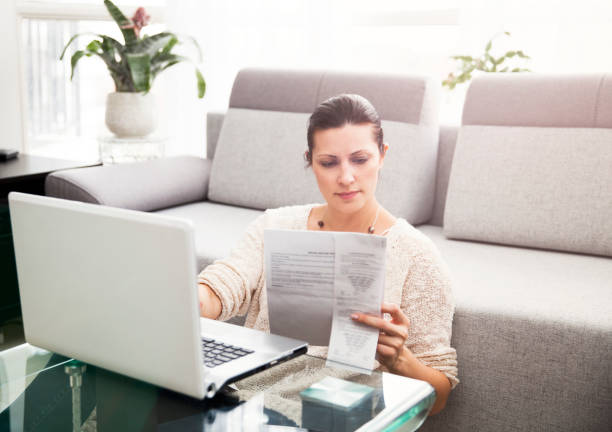 Woman Filing Income Tax Online Woman in her 30s filling out tax information online taxes stock pictures, royalty-free photos & images